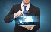 Businessman hand holding magnifier over tablet pc — Stock Photo