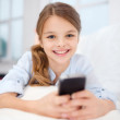 Smiling girl with smartphone at home — Stock Photo #39805179