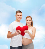 Happy young family expecting child with big heart — ストック写真
