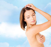 Woman checking breast for signs of cancer — 图库照片