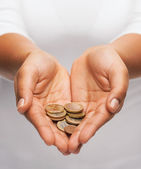 Womans cupped hands showing euro coins — Stock Photo