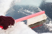 Woman cleaning snow from car back window — Stock Photo