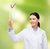 Smiling female doctor pointing to checkbox — Stockfoto