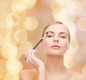 Beautiful woman with makeup brush — Stock Photo