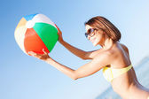 Girl in bikini playing ball on the beach — Foto Stock