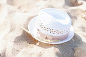 White straw hat lying in the sand on the beach — Stock Photo