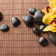 Massage stones with flowers on mat — Stock Photo