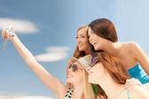 Lachende meisjes nemen van foto in café op het strand — Stockfoto