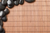 Massage stones on bamboo mat — Stock Photo
