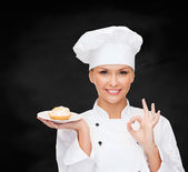 Smiling female chef with cake on plate — Stock fotografie