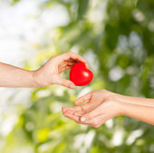 Man hand giving red heart to woman — Stock Photo