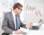 Uomo d'affari con computer, carte e calcolatrice — Foto Stock