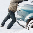 Closeup of man pushing car stuck in snow — Stock Photo #40108895