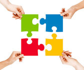Four hands connecting puzzle pieces — Stock Photo