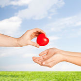 Man hand giving red heart to woman — Stockfoto