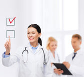 Smiling female doctor pointing checkbox — Stock Photo