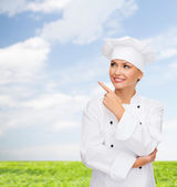 Smiling female chef pointing finger to sonething — Stock Photo