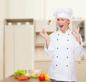 Smiling female chef with fork and tomato — Stock fotografie
