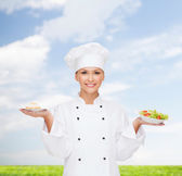 Smiling female chef with salad and cake on plates — Foto de Stock