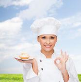 Sonriente mujer chef con pastel en placa — Foto de Stock