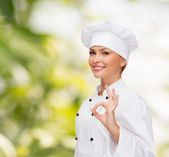 Smiling female chef showing ok hand sign — Stockfoto
