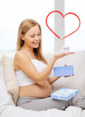 Smiling pregnant woman with gift box and bootees — Stock Photo