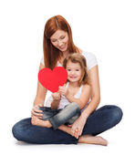 Happy mother with adorable little girl and heart — Stock Photo
