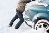 Closeup of man pushing car stuck in snow — Stock Photo