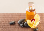 Essential oil, massage stones and orchid flower — Foto Stock