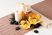 Essential oil, massage stones and orchid flower — Stockfoto