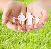 Female hands with paper man family — Stock Photo