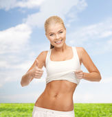 Sporty woman showing thumbs up — Stock Photo