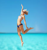 Happy woman jumping on the beach — Stock Photo