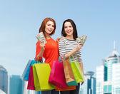 Sorrindo adolescentes com sacos de compras e dinheiro — Fotografia Stock