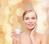 Woman applying cream on her skin — Stock Photo