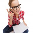 Smiling teenage girl in eyeglasses reading book — Stock Photo #40172479