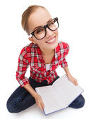 Smiling teenage girl in eyeglasses reading book — Stock Photo