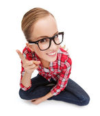 Smiling teenager in eyeglasses with finger up — Stock Photo