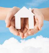Vrouwelijke handen met papier huis — Stockfoto