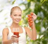 Woman holding glass of juice and tomatoes — Stock Photo