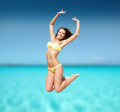Woman in bikini jumping on the beach — Foto Stock