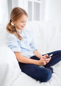 Smiling girl with smartphone at home — Stock Photo