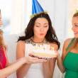 Three women wearing hats holding cake with candles — Stock Photo #40313463