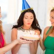 Three women wearing hats holding cake with candles — Stock Photo