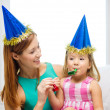 Mother and daughter in blue hats with favor horns — Stock Photo #40313503