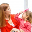 Stock Photo: Happy mother and daughter with comb