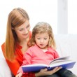 Happy mother and daughter with book — Stockfoto #40314539