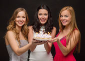Three women holding cake with candles — Stok fotoğraf