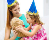 Mother and daughter in blue hats with teddy bear — Stock Photo