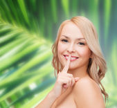 Beautiful young woman pointing finger to lips — Stock Photo